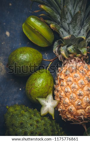 ripe tropical fruits on a concrete turquoise background