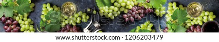 Ripe twig of grapes with a glass of sparkling wine on a dark background.
