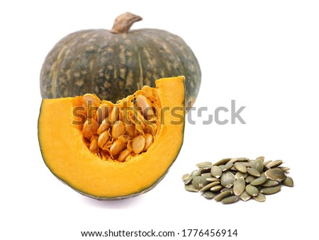 Ripe uncooked pumpkin and a cut into piece and pile of cooked pumkin seeds are isolated on white background.