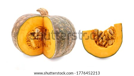 Ripe uncooked pumpkin and a cut into piece are isolated on white background.