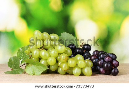 Ripe white and red grapes on  green background
