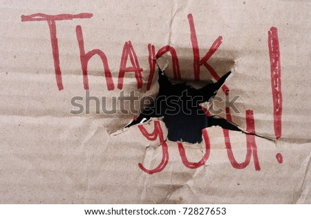 ripped cardboard with red sign (Thank you!) and large bullet hole in it - stock photo