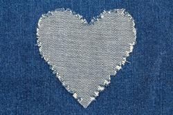 Ripped denim heart frame on denim jeans background. Denim jeans fashion background.