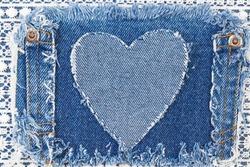 Ripped denim heart frame on Destroyed torn denim blue jeans patch pocket  on white lace background. Denim jeans fashion background