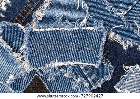 Ripped denim patch on destroyed torn denim blue jeans. Double color denim jeans fashion background