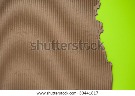 Ripped torn corrugated cardboard textured background with green knock out