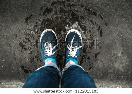 Ripple Effect Caused by Feet Stomping In a Puddle During a Rainstorm