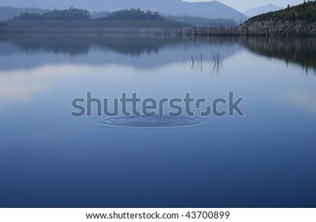 Ripple in still waters on a misty day, Strathgordon, Tasmania - stock photo