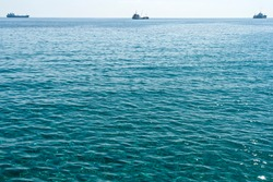 Rippled  glistening sea water surface with three ships on the horizon