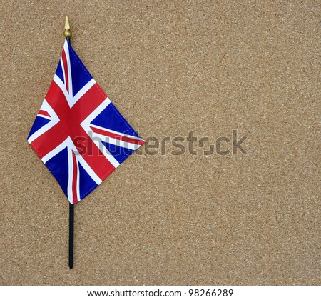 Ripples in Great Britain British Flag on flagpole isolated on cork board background with room for your text