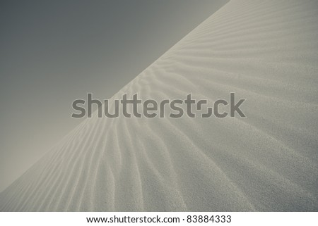 Ripples in sand dunes in black and white - stock photo