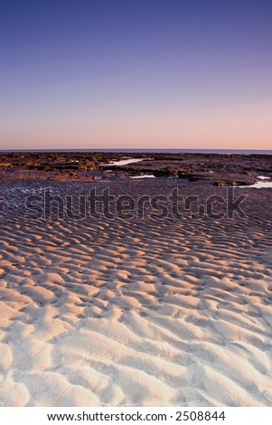 Ripples in the sand during low tide at sunrise.