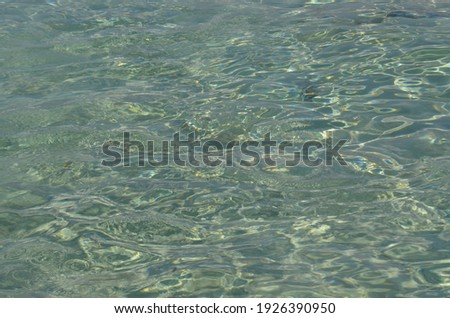 Rippling sea water surface with sun glare. Nature background texture. Golden beach, Chrissi island, Greece.