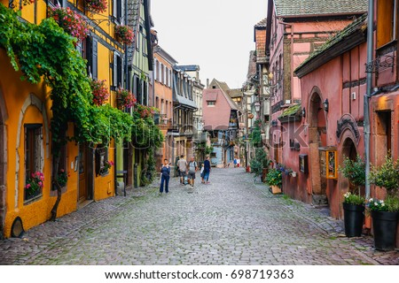RIQUEWIHR, FRANCE - July 11, 2017:  Main street houses in the beautiful french village in Eastern Alsace, France #698719363