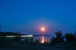 Rise of a bloody, red, moon, full moon, over a large river at night