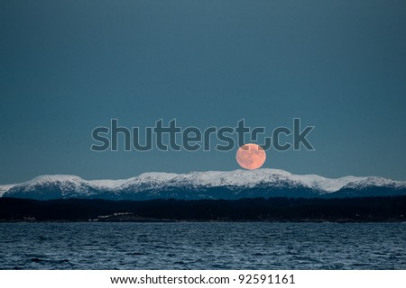 Rise up of beautiful red moon over the snowy Norwegian mountains