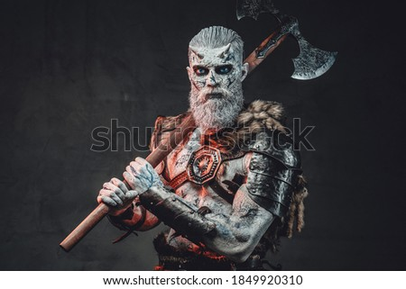 Risen from the dead king with pale skin and horns dressed in dark armour in twilight with hatchet on his shoulder. Stock photo ©