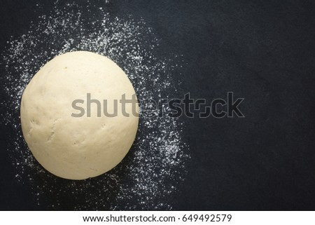 Risen or proved yeast dough for bread or pizza on a floured slate surface, photographed overhead with natural light (Selective Focus, Focus on the top of the dough)