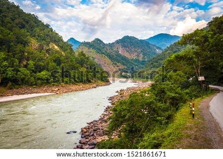 Rishikesh, Yoga city India, Ganga River valley, Sunrise Uttarakhand. River rafting Landscape of mountains in Rishikesh along side river Ganga flowing in the monsoon season in Uttarakhand, India. Image Foto stock ©