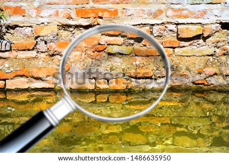 Rising damp on a brick wall in a channel full of water - Concept image seen through a magnifying glass