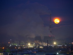 Rising large orange moon over the CHP. Full moon over a smoking factory, pipes of a thermal power plant. The moon next to the high tube of the plant