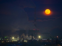 Rising large orange moon over the CHP. Full moon over a smoking factory, pipes of a thermal power plant.