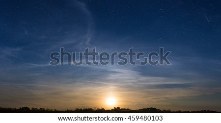 Rising moon in dark blue sky with stars over the meadow. Natural astronomy background
