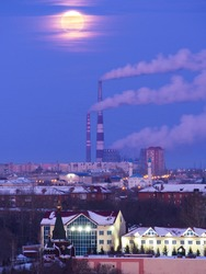 Rising moon over Omsk: chapel, temple of all Saints, CHP-5 and a mosque. The moon is large, only appears from behind the clouds, hidden by a veil of clouds.