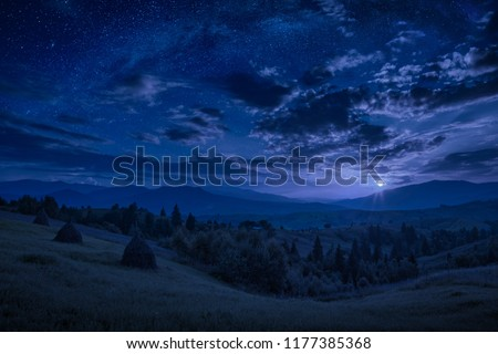 Rising of the full moon in a mountain valley with stars in a cloudy night sky. Dramatic and picturesque scene. Carpathians, Ukraine. Beautiful world.