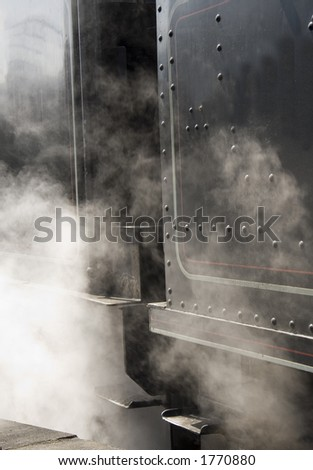 Rising steam from the side of a steam engine.