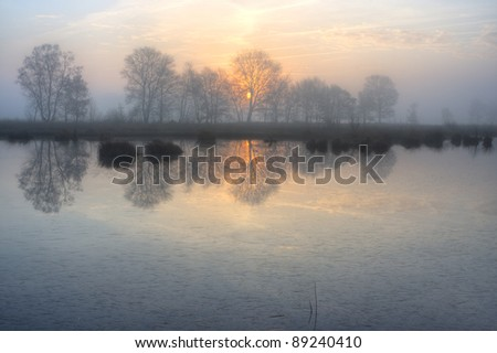 Rising sun and tree silhouettes reflected on a frozen lake