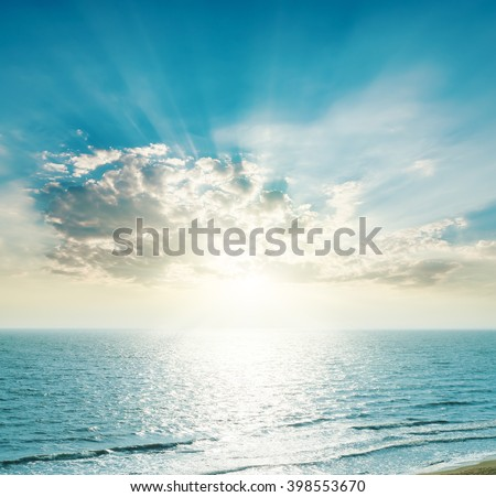 rising sun on the horizon, blue sea and clouds #398553670