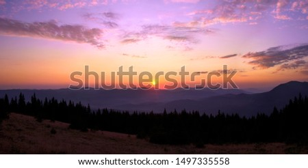 Rising sun with colorful skyline over the mountains in early morning