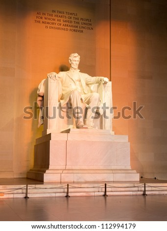 Rising sunrise at dawn lights statue of President Lincoln in memorial in Washington DC