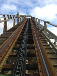 Rising to the top of a wooden rollercoaster from the perspective of the first seat