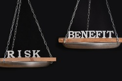 Risk and benefit reward concept. Scales on black background close up.