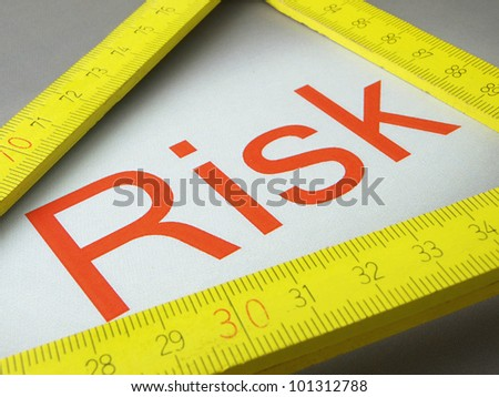 Risk and measure words A wooden ruler and measurement of the written word - stock photo