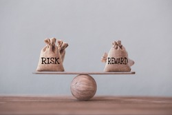 Risk and reward bags on a basic balance scale in equal position on wood table. risk management concept, depicts investors use a risk reward ratio to compare the expected return of an investment