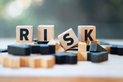 Risk assessment, decision to accept business result in uncertainty, unpredictable situation concept, cube wooden block with alphabet building the word RISK.