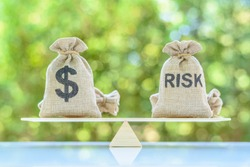Risk assessment / risk analysis and management concept : Dollar and risk bags on basic balance scale, depict evaluation of financial risk that investor involved in stock, futures and derivative market