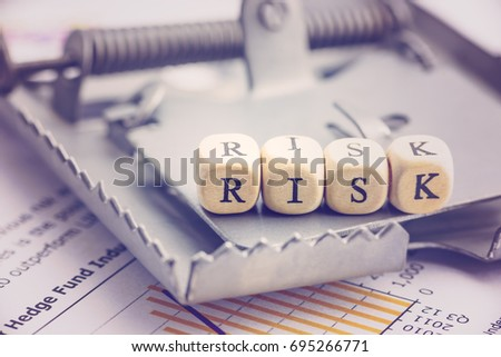 Risk management and risk tolerance concept : Dices are put in a word RISK on a rat trap, risk is a probability or threat of damage, liability, loss and may be avoided through preemptive action.