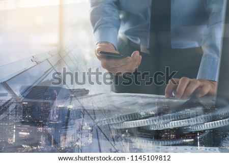 Risk management, business investment concept. Trader, business man using mobile phone working, monitoring on stock exchange report on laptop computer with financial background and the city.