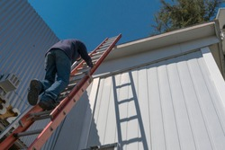Risks of a worker climbing uninsured ladder to work on the roof of a house on a beautiful sunny day with blue sky.
