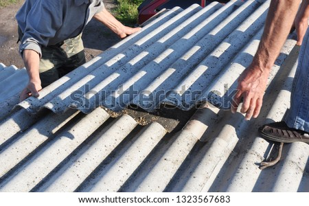 Risks of Asbestos Roofs, Asbestos Roof Removal. Asbestos removal roof works. House with old, danger asbestos roof tiles repair.