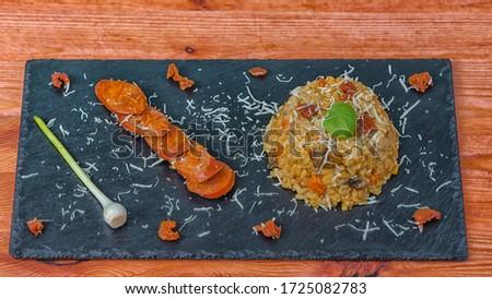 Risotto chorizo parmesan black plate top Stock fotó ©