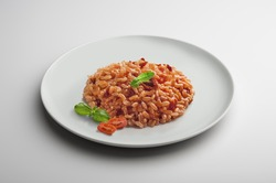 Risotto dish with dried tomatoes and basil isolated on white table