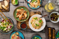 Risotto with cherry tomatoes, basil and parmesan cheese, roasted chicken legs, snacks and lemonade on a wooden table. Italian food table