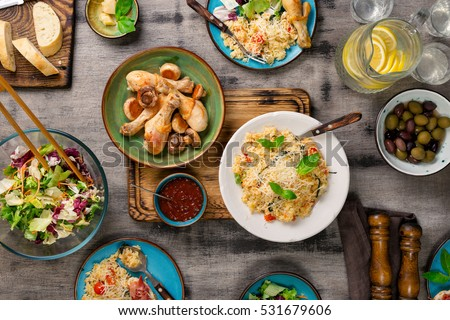 Risotto with cherry tomatoes, basil and parmesan cheese, roasted chicken legs, snacks and lemonade on a wooden table. Italian food table #531679606