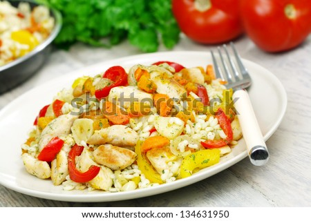 Risotto with chicken and vegetables on a wooden table