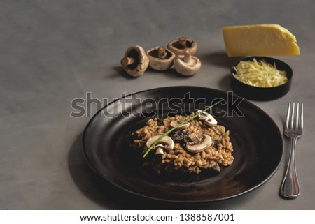 Risotto with funghi mushrooms and parmesan cheese in a dark plate with wine Foto d'archivio ©